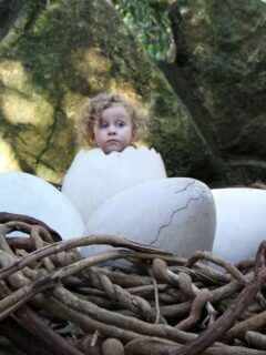 A toddler pretends to hatch from a giant egg at the Xcaret Aviary exhibit