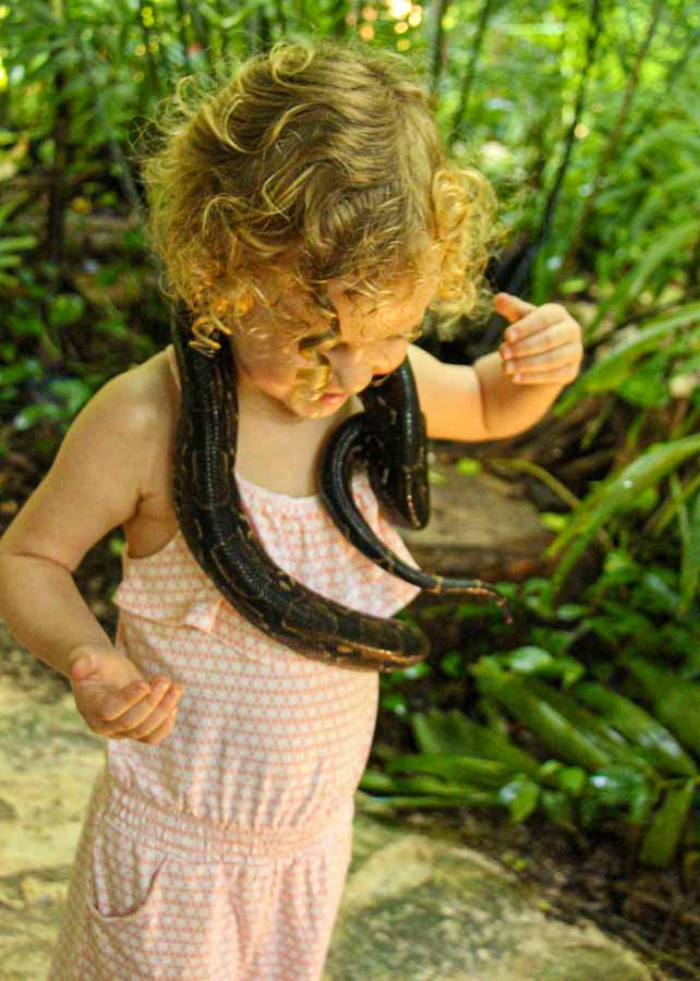 A brave 4-year old girl holds a snake at the CroCo Cun zoo near Puerto Morelos