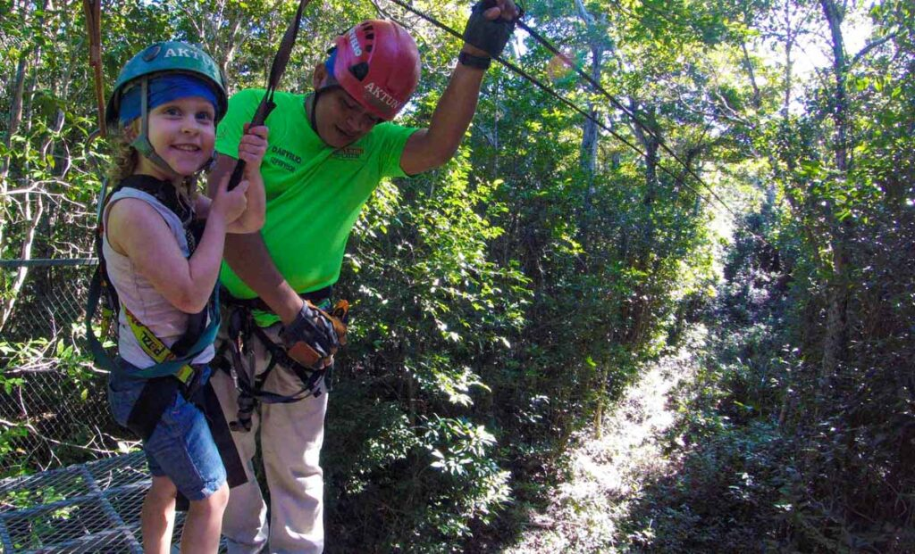 a 4-year old girl loves the ziplines at Aktun Chen Natural Park in the Yucatan Penninsula