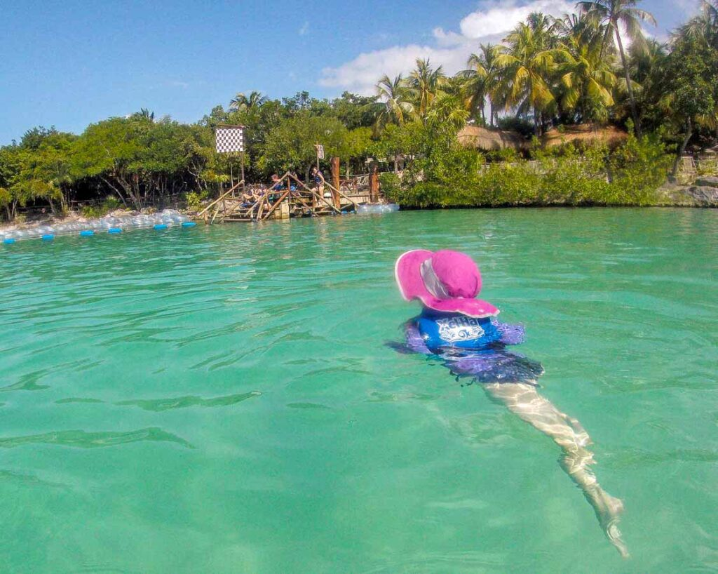 a 4-year old swims the Xel-Ha river after a fun tube ride