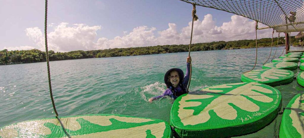 A 4-year old loves trying to cross the trail of lily pads at Xel-Ha Children's World