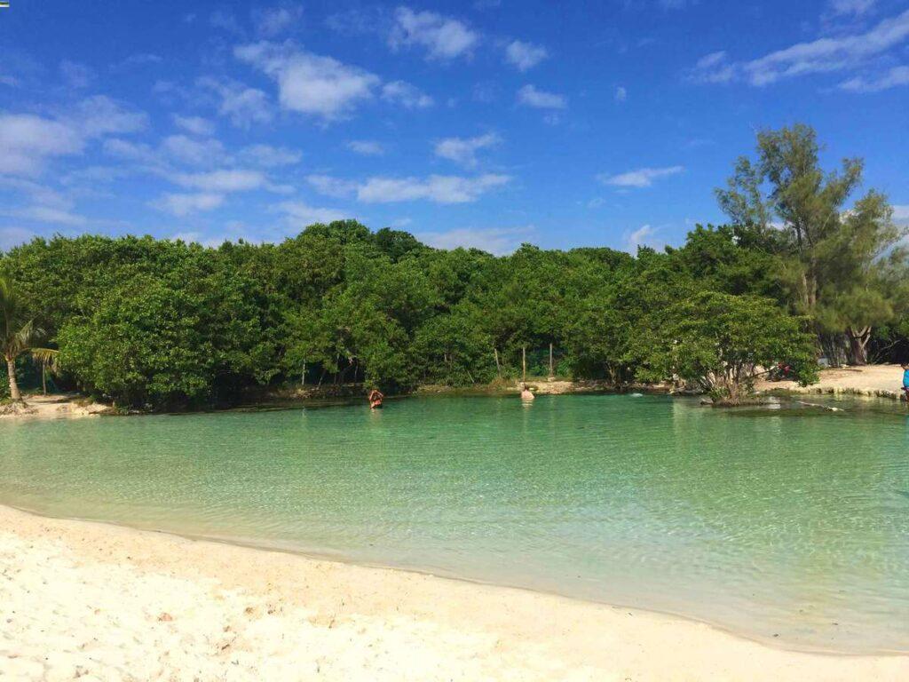 Enjoy a swim in a fresh water cenote at Esmeralda Beach in Playa del Carmen