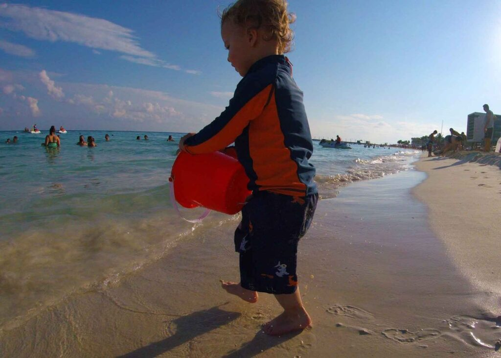 A toddler plays on Playa Mamitas - one of the best beaches in Playa del Carmen