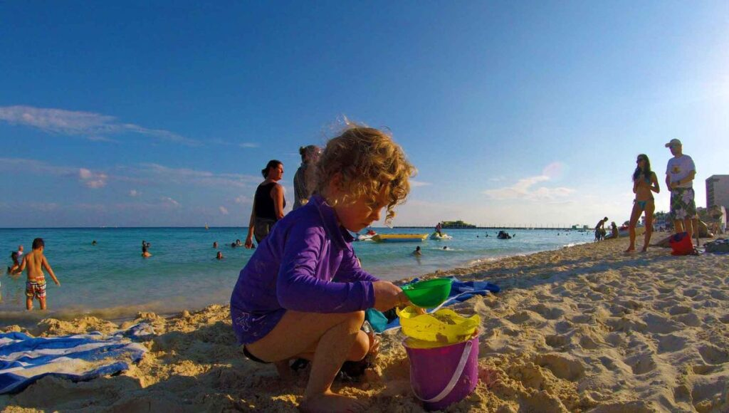 A child plays in the sand in front of mamitas beach club playa del carmen mexico