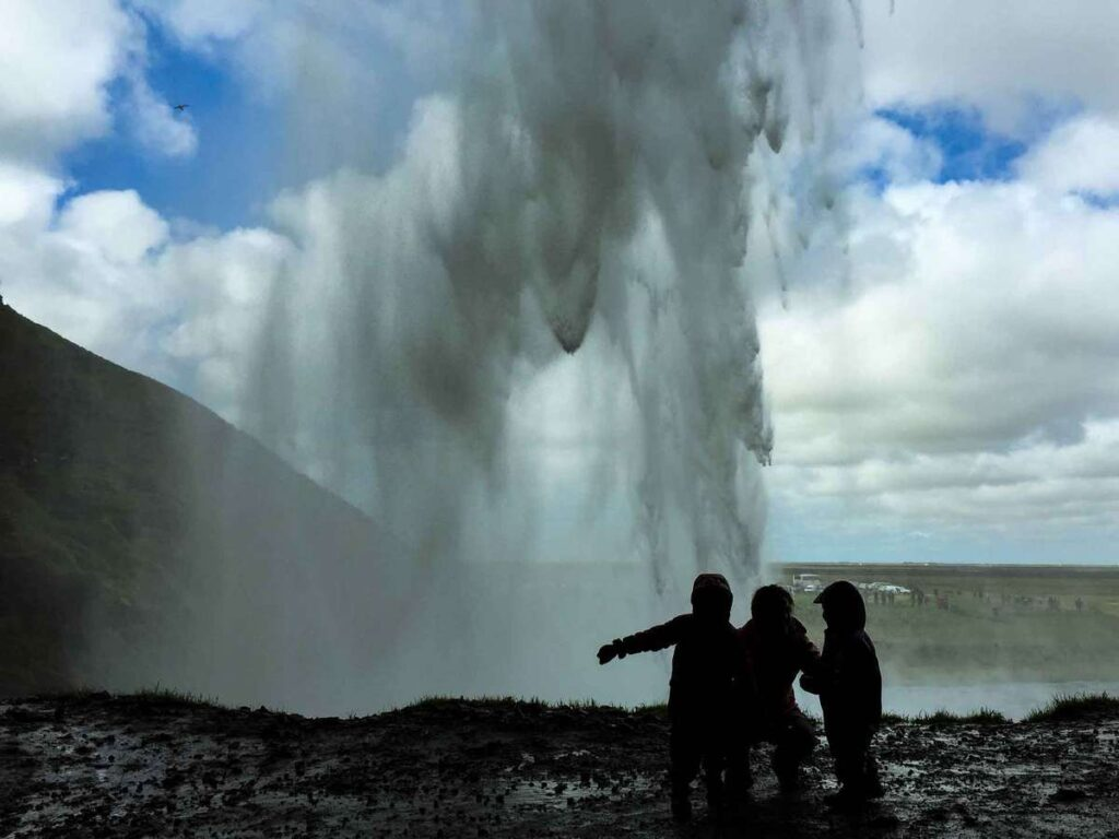 what is there to do in iceland for kids - Walking behind Seljalandsfoss waterfall in South Iceland