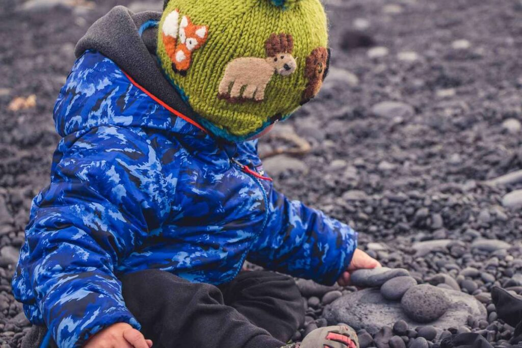 things to do on the Snaefellsnes Peninsula with kids - Playing with black rocks on Djupalonssandur Beach -Snaefellsjoekull National Park Iceland