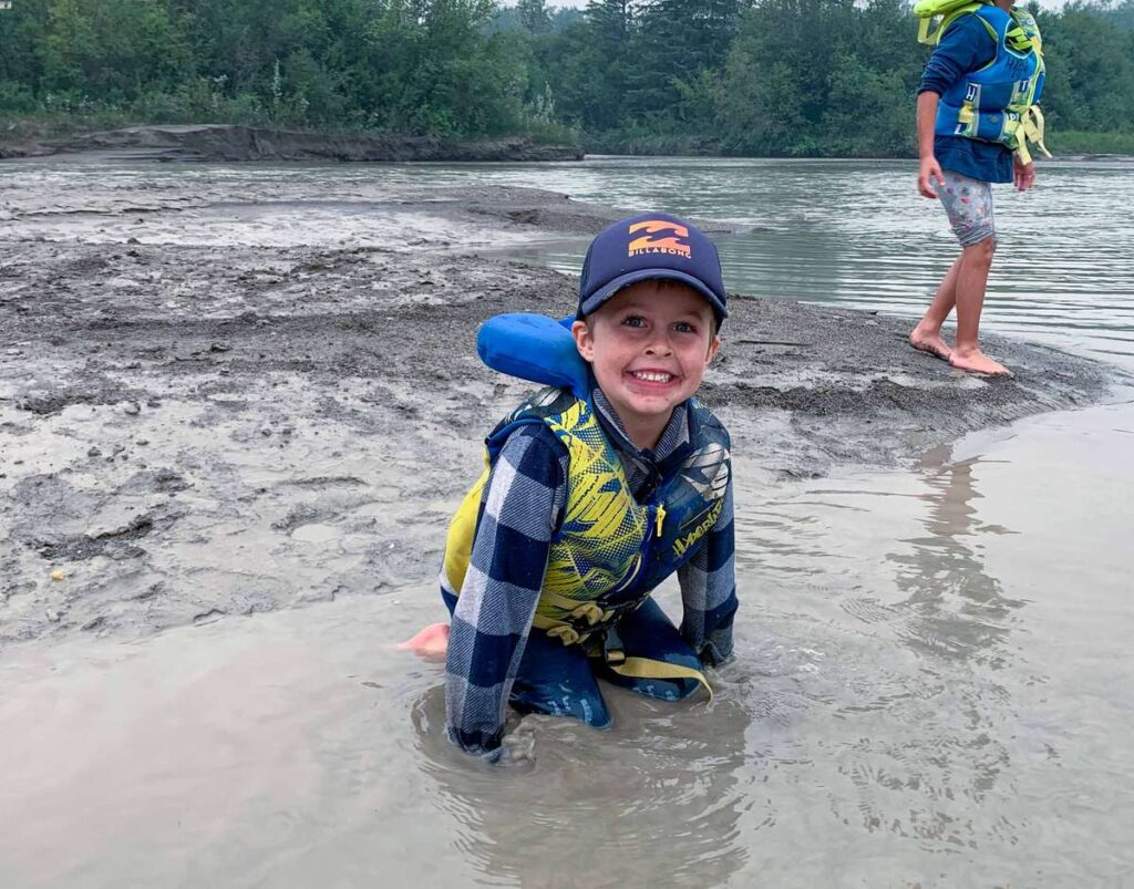 enjoying time in the mud while canoeing from Invermere to Radium Hot Springs with our kids